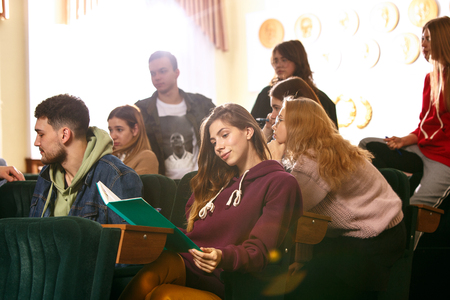 The group of cheerful students sitting in a lecture hall before lesson. The education. University lecture  and communication concept.