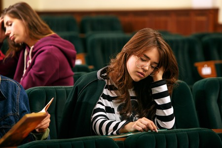 The group of cheerful students sitting in a lecture hall before lesson. The education, university, lecture, people, institute, college, studying, friendship and communication concept Stok Fotoğraf - 113938540