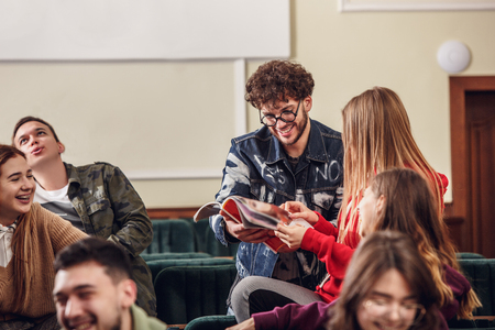 The group of cheerful students sitting in a lecture hall before lesson. The education, university, lecture, people, institute, college, studying, friendship and communication concept Stok Fotoğraf