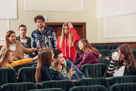 The group of cheerful students sitting in a lecture hall before lesson. The education, university, lecture, people, institute, college, studying, friendship and communication concept Zdjęcie Seryjne