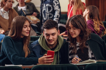 The group of cheerful students sitting in a lecture hall before lesson. The education, university, lecture, people, institute, college, studying, friendship and communication concept Stock fotó