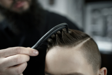 Children hairdresser cutting little boys hair. Contented cute preschooler boy getting the haircut. Stockfoto - 113939404