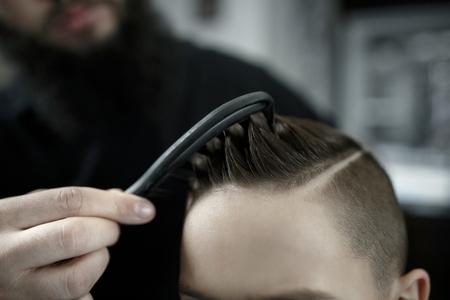 Kinderkapper die het haar van kleine jongens knippen. Tevreden schattige kleuterjongen die het kapsel krijgt.
