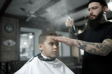 Children hairdresser cutting little boys hair. Contented cute preschooler boy getting the haircut.