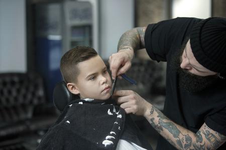 Children hairdresser shaving little boy. Contented cute preschooler boy getting the haircut.