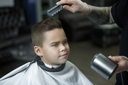 Children hairdresser cutting little boys hair. Contented cute preschooler boy getting the haircut.