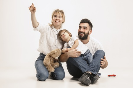 The happy family with kid sitting together and smiling at camera isolated on white studio background Zdjęcie Seryjne