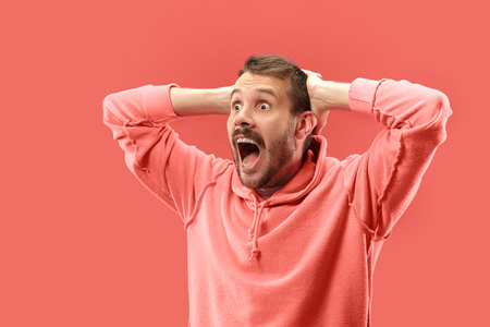 Wow. Attractive male half-length portrait on coral studio backgroud. Young emotional surprised bearded man standing with open mouth. Human emotions, facial expression concept. Trendy colors