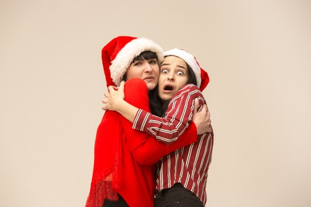 A portrait of a scared mother and daughter in Santa hat at studio on gray background. Trendy colors. Human positive emotions and facial expressions concept Reklamní fotografie