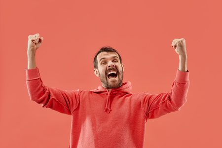 I won. Winning success happy man celebrating being a winner. Dynamic image of caucasian male model on coral studio background. Victory, delight concept. Human facial emotions concept. Trendy colors