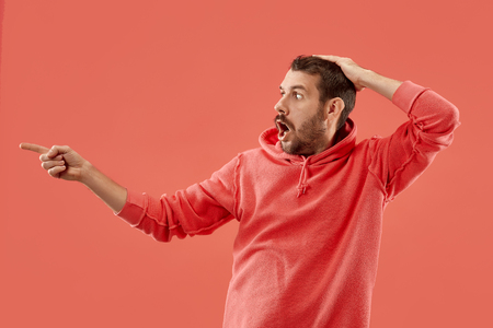 Wow. Attractive male half-length front portrait on coral studio backgroud. Young emotional surprised bearded man standing with open mouth. Human emotions, facial expression concept. Trendy colors