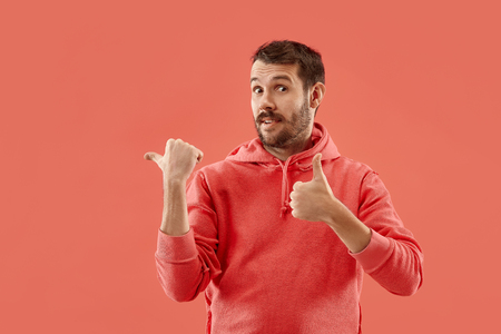 Wow. Attractive male half-length front portrait on coral studio backgroud. Young emotional surprised bearded man pointing to left. Human emotions, facial expression concept. Trendy colors