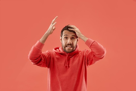 Why is that. Beautiful male half-length portrait isolated on trendy coral studio backgroud. Young emotional surprised, frustrated and bewildered man. Human emotions, facial expression concept.