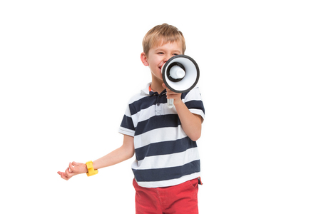 Little cute kid baby boy holding in hand and speaking in electronic gray megaphone isolated on white background. Kids childhood lifestyle concept. Copy space