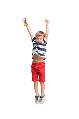 Adorable blond boy jumping and raises his hands up. Isolated on white background. Shooting in the studio