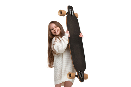portrait of an adorable young girl riding a skateboard isolated against white background at studio Stock Photo