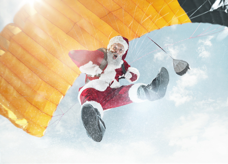 Merry Christmas and happy holidays. Santa Claus flying with parachute over background of blue sky.