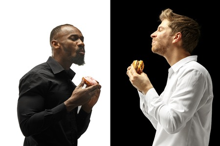 Men eating a hamburger and donut on a black and white background. The happy afro and caucasian men. The burger, fast, unhealthy food concept Standard-Bild - 114731947