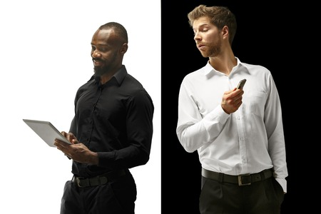 The success happy afro and caucasian men. Mixed couple with gadget. Dynamic image of male models on white and black studio. Human facial emotions concept.