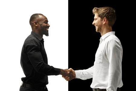 friendly handshake.The success happy afro and caucasian men. Mixed couple. Dynamic image of male models on white and black studio. Human facial emotions concept.