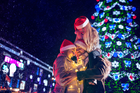 family, christmas, holidays, season and people concept - happy family over lights city background and snow at night Banque d'images - 115007076