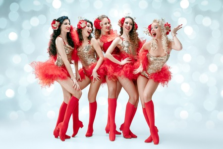 The group of young happy smiling beautiful female dancers with carnival dresses posing on blue studio background