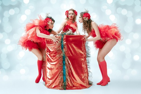 The group of young happy smiling beautiful female dancers with carnival dresses posing with big gift on blue studio background