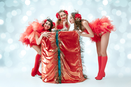 The group of young happy smiling beautiful female dancers with carnival dresses posing with big gift on blue studio background Stock Photo - 115008269