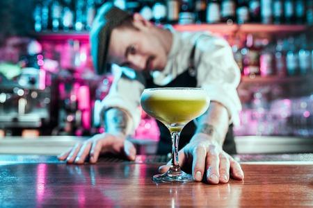 Deskundige barman maakt cocktail in nachtclub of bar. Glas vurige cocktail op de toog tegen de achtergrond van barmannenhanden met vuur. Barman dag concept