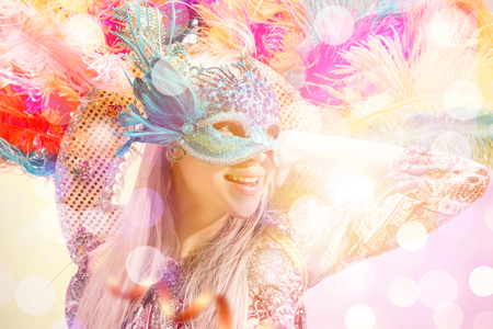 Beautiful young woman in carnival mask. Beauty model woman wearing masquerade mask at party over holiday background with magic glow. Christmas and New Year celebration. Glamour lady with perfect make up and hairstyle Фото со стока