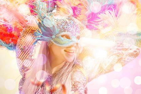 Schöne junge Frau in Karnevalsmaske. Schönheitsmodellfrau, die Maskerademaske auf Party über Feiertagshintergrund mit magischem Glühen trägt. Weihnachts- und Neujahrsfeier. Glamour Lady mit perfektem Make-up und Frisur Standard-Bild