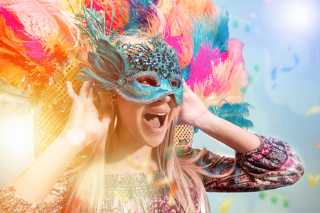 Beautiful young woman in carnival mask. Beauty model woman wearing masquerade mask at party over holiday background with magic glow. Christmas and New Year celebration. Glamour lady with perfect make up and hairstyle Stock Photo