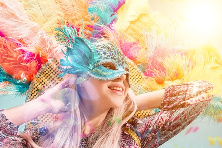 Beautiful young woman in carnival mask. Beauty model woman wearing masquerade mask at party over holiday background with magic glow. Christmas and New Year celebration. Glamour lady with perfect make up and hairstyle 版權商用圖片