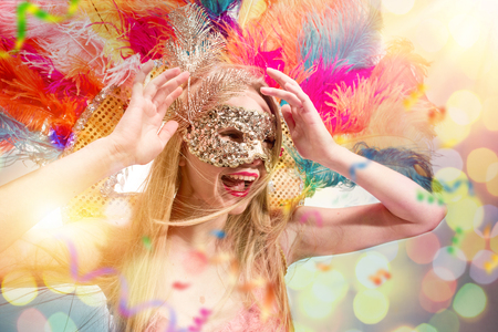 Beautiful young woman in carnival mask. Beauty model woman wearing masquerade mask at party over holiday background with magic glow. Christmas and New Year celebration. Glamour lady with perfect make up and hairstyle Zdjęcie Seryjne
