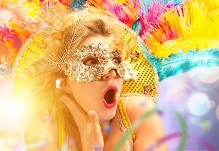 Beautiful surprised woman in carnival mask. Beauty model woman wearing masquerade mask at party over holiday background with magic glow. Christmas and New Year celebration. Glamour lady with perfect make up