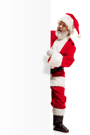 Happy surprised Santa Claus pointing on blank advertisement banner