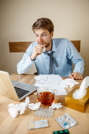 Feeling sick and tired. The man with cup of hot tea working in office, businessman caught cold, seasonal flu.