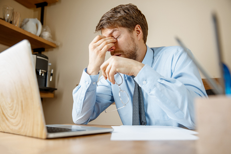 Feeling sick and tired. Frustrated sad unhappy sick young man massaging his head while sitting at his working place in office. Stockfoto