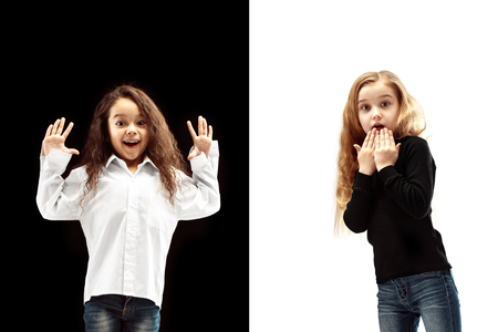The portrait of two happy surprised girls on a white and black studio