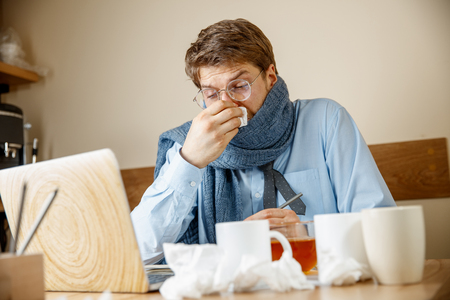 Sick man with handkerchief sneezing blowing nose while working in office, businessman caught cold, seasonal flu.