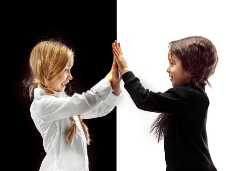 Hand shake and high five. The portrait of two happy holding hands girls on a white and black studio
