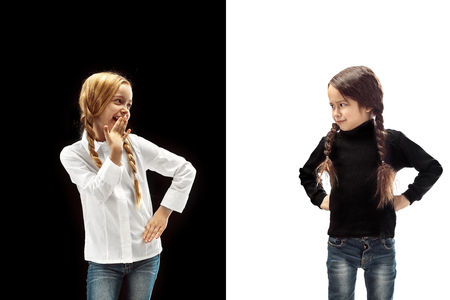 The portrait of emotional happy winner girl and serious angry girl on a white and black studio