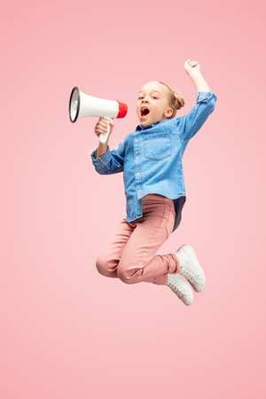 Beautiful young child teen girl jumping with megaphone isolated over pink 写真素材 - 115527107