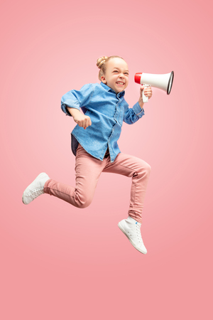 Beautiful young child teen girl jumping with megaphone isolated over pink