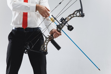 Businessman aiming at target with bow and arrow, isolated on gray studio Imagens - 115526317