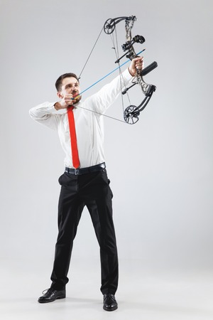 Businessman aiming at target with bow and arrow, isolated on gray studio