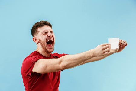 Young boy with a surprised happy expression bet slip on blue studio