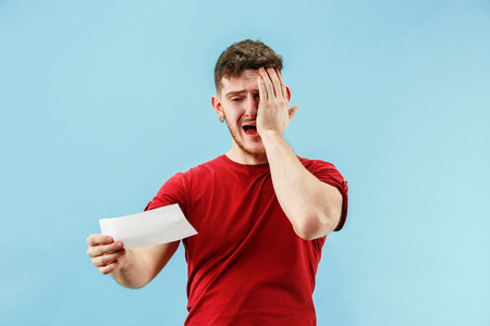Young boy with a surprised unhappy failure expression bet slip on blue studio