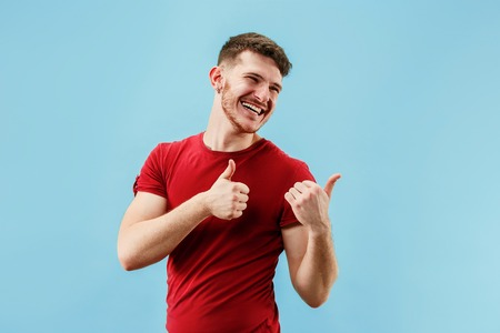 Do not miss. Young casual man shouting. Shout. Crying emotional man screaming on blue studio background. male half-length portrait. Human emotions, facial expression concept. Trendy colors 免版税图像