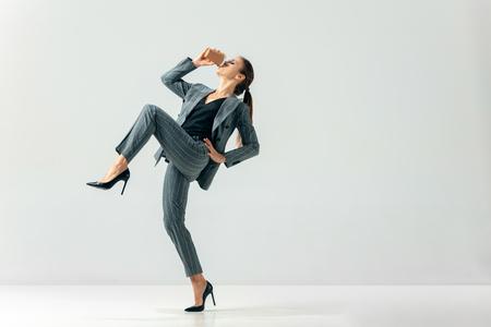 Mujer de negocios feliz bailando y sonriendo en movimiento aislado sobre fondo blanco de estudio. Concepto de emociones humanas. La empresaria, oficina, éxito, profesional, felicidad, conceptos de expresión